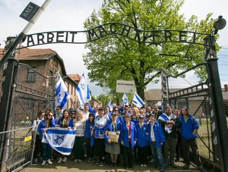 Members of the UK delegation underneath the infamous Auschwitz gates, which bear the slogan 'Work makes you free'. Photo: Sam Churchill